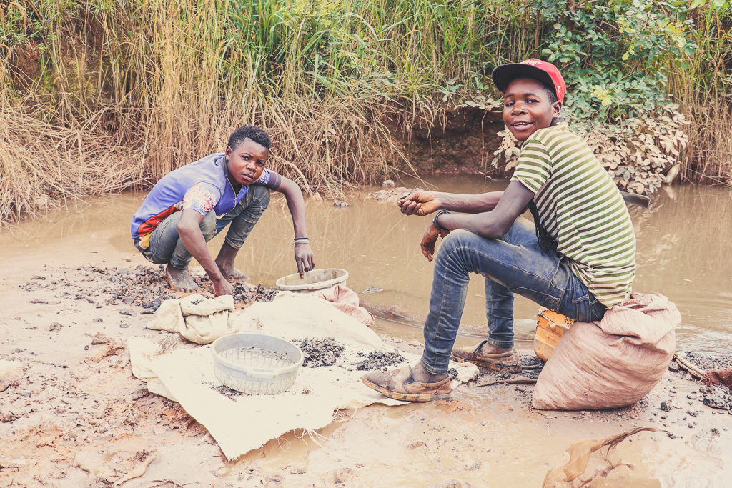 two young miners washing the ore impact facility